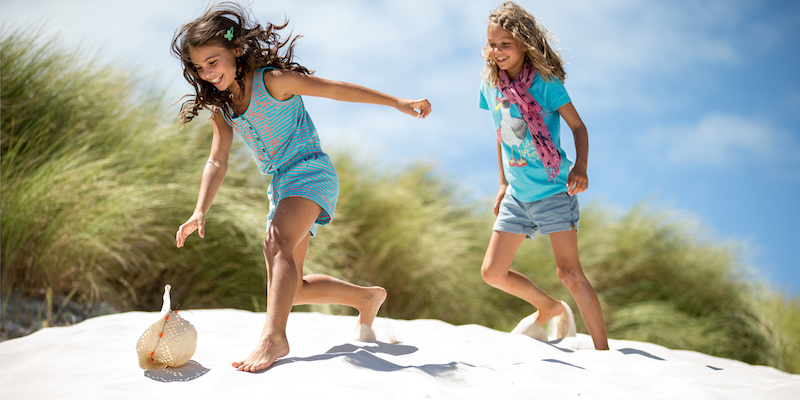 Two girls running in the sand
