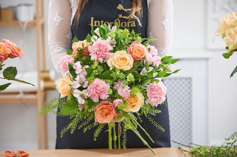 An Interflora florist arranges flowers