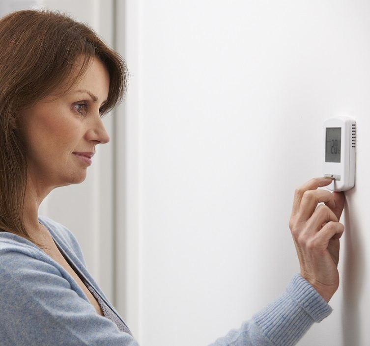 Woman using a thermostat
