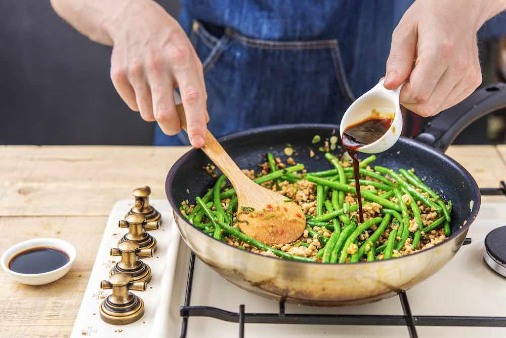 A man adding soy sauce to his pan of green beans